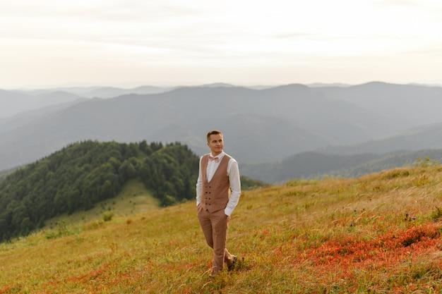 Pan młody idzie samotnie na tle jesiennych gór.