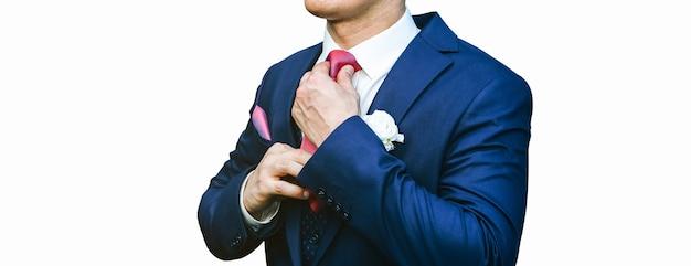 Pan młody na białym tle. niebieski ślubny garnitur i czerwony krawat. stylowe detale.