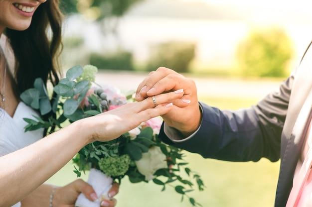 Pan młody nosi narzeczoną obrączkę podczas ceremonii.