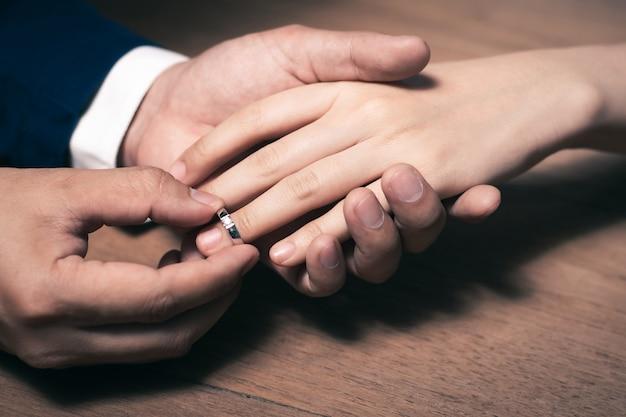Pan młody nosi obrączkę do palca panny młodej.