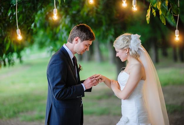 Pan młody nosi pierścień dla panny młodej pod łukiem lamp oświetleniowych