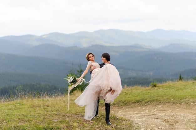 Pan młody nosi w ramionach swoją oblubienicę. fotografia ślubna w górach.