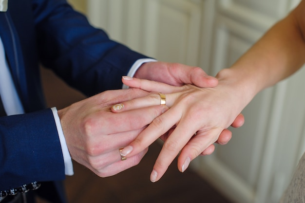 Pan młody nosi złoty pierścionek na palcu panny młodej.
