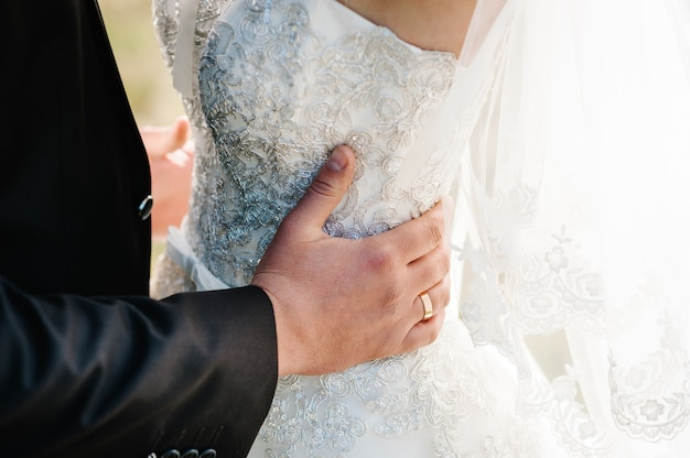 Pan młody obejmuje pannę młodą rękami za talią i stojąc na ceremonii ślubnej na świeżym powietrzu na podwórku przyrody.