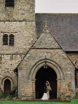 Pan młody obejmuje pannę młodą w pobliżu starego kościoła angielskiego, pochmurny dzień.