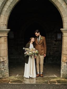 Pan młody obejmuje pannę młodą w pobliżu wejścia do starego kościoła angielskiego, pochmurny dzień