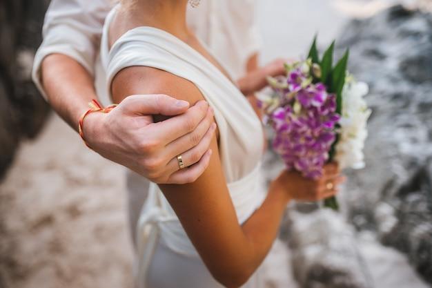 Pan młody obejmuje ramiona panny młodej z bukietem fotografia ślubna