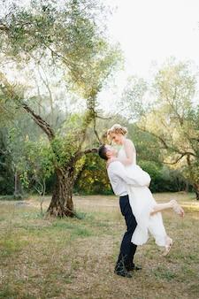 Pan młody okrąża pannę młodą w ramionach wśród drzew w gaju oliwnym, panna młoda się uśmiecha