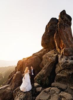 Pan młody patrzy na swoją żonę, stojąc na wysokiej, ogromnej skale