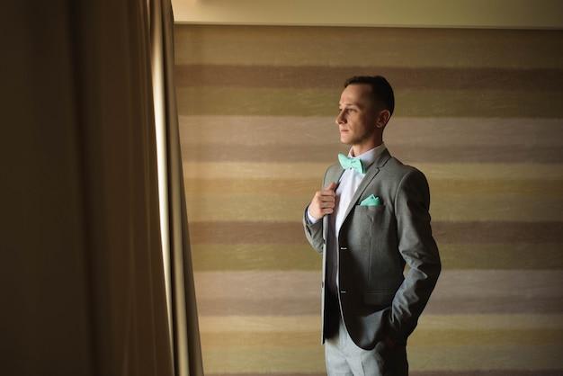 Pan młody przygotowuje się rano przed ceremonią ślubną, zakładając kurtkę na koszulę w pokoju.