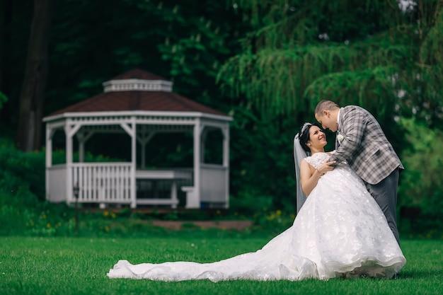 Pan młody przytula pannę młodą, a ona ugina jej plecy. nowożeńcy w parku na tle altanki. panna młoda w sukni ślubnej z długim ogonem.