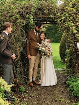 Pan młody przytula pannę młodą po ceremonii ślubnej. ceremonia ślubna w ogrodzie
