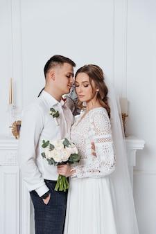 Pan młody przytula pannę młodą w koronkowej sukni ślubnej w stylu boho w przytulnym pokoju.