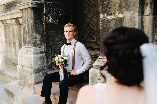 Pan młody siedzi na kamiennych schodach i pozuje do kamery