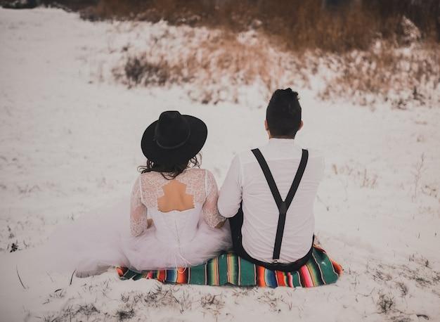 Pan młody siedzi z panną młodą w białej sukni ślubnej i czarnym kapeluszu na meksykańskim welonie na zaśnieżonym wzgórzu