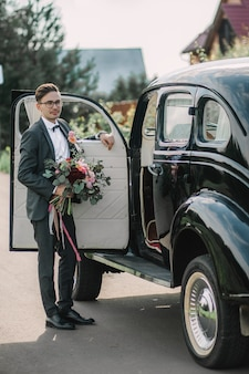 Pan młody stoi przy samochodzie i czeka na pannę młodą w dniu ślubu.