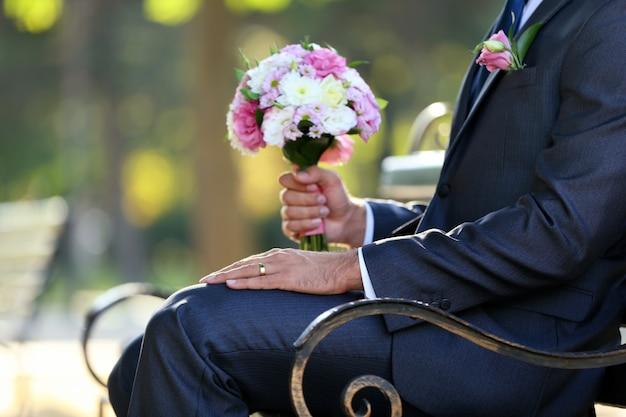 Pan młody trzyma bukiet ślubny na zewnątrz