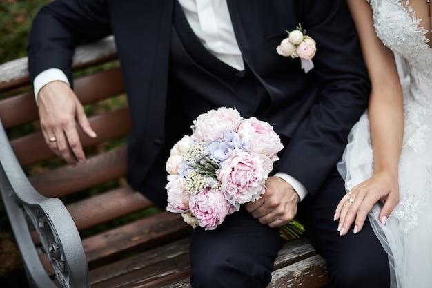 Pan młody trzyma bukiet ślubny w rękach stojących w pobliżu panny młodej