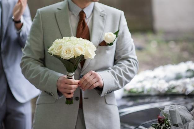 Pan młody trzyma bukiet ślubny z białych róż.