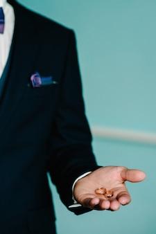Pan młody trzyma obrączki na dłoni, pan młody w niebieskim garniturze, mężczyzna trzyma obrączki, obrączkę pana młodego w dłoni. zaręczynowy.
