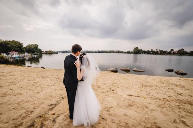 Pan młody trzyma pannę młodą na piasku w pobliżu jeziora.