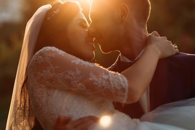 Pan młody trzyma pannę młodą w ramionach i całują. wieczorne słońce oświetla nowożeńców. ścieśniać.