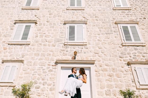 Pan młody trzyma pannę młodą w ramionach przy kamiennej ścianie budynku w jasny, słoneczny dzień