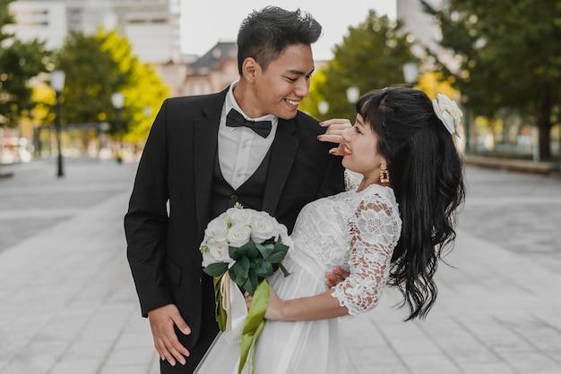 Pan młody trzyma pannę młodą za jej plecami w romantycznej pozie