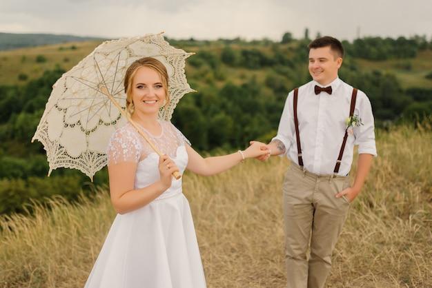 Pan młody trzyma pannę młodą za rękę na weselu z pięknym krajobrazem