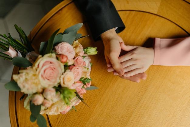 Pan młody trzyma pannę młodą za rękę. zbliżenie. kochająca panna młoda i pan młody siedzą w kawiarni.