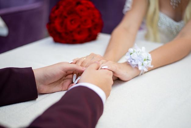 Pan młody trzyma panny młode za ręce