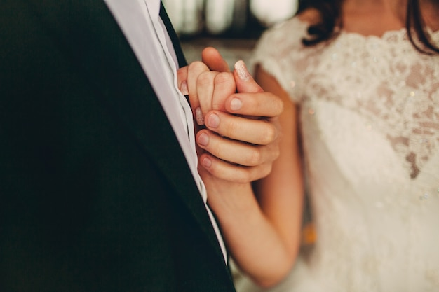 Pan młody trzyma rękę młodej w pobliżu serca