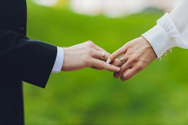 Pan młody trzyma rękę panny młodej na ceremonii ślubnej. trzymaj się za ręce i chodź razem.