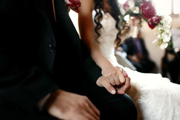 Pan młody trzyma rękę panny młodej na kolanie