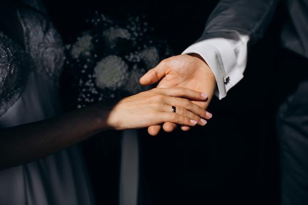 Pan młody trzyma rękę panny młodej w ręce
