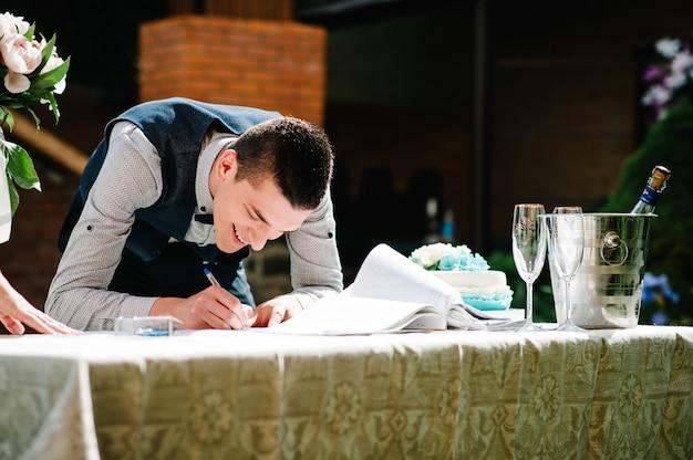 Pan młody trzyma w dłoni długopis i pisze tak w czasopiśmie małżeńskim.