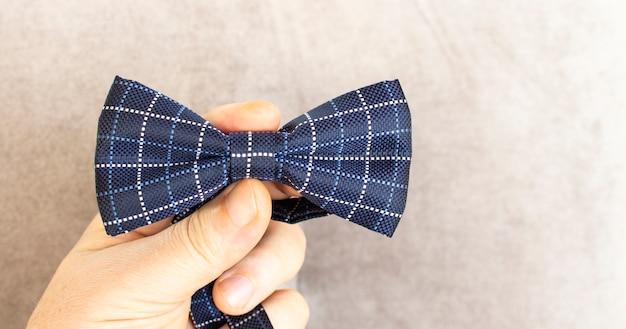 Pan młody trzyma w rękach niebiesko-białą muszkę w kropki, klasyczną z materiału tekstylnego. motyl to jeden z elementów męskiej garderoby. wakacje, wesele, impreza.