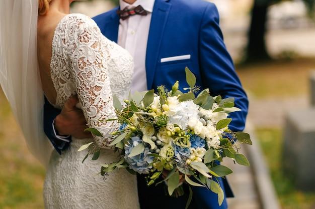 Pan młody trzyma wspaniały bukiet ślubny, podczas gdy on przytula pas młodej oblubienicy