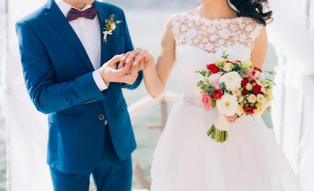 Pan młody ubiera pierścionek na palcu panny młodej na ceremonii ślubnej