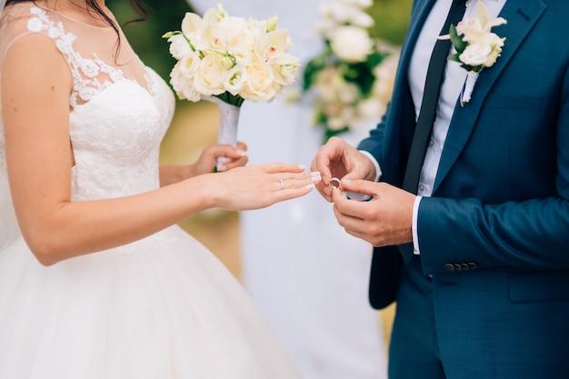 Pan młody ubiera pierścionek na palcu panny młodej na weselu