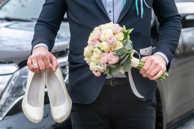 Pan młody ubrany w niebieski garnitur trzyma bukiet ślubny róż i białe kobiece buty ślubne na tle samochodu.