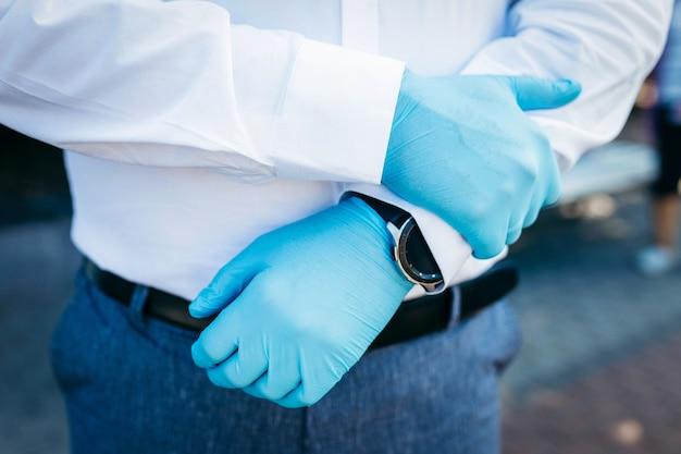 Pan młody w białej koszuli i gumowych rękawiczkach trzyma ręce przed sobą