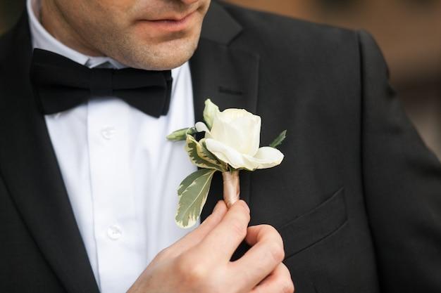 Pan młody w białej koszuli, motylu i czarnym garniturze prostuje dziurkę od guzika.