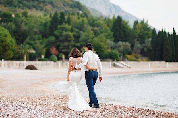 Pan młody w białej koszuli przytula pannę młodą w białej koronkowej sukience nowożeńcy spacerują wzdłuż plaży