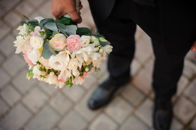 Pan młody w czarnym garniturze i klasycznych butach z bukietem ślubnym