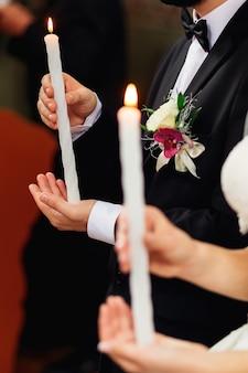 Pan młody w czarnym garniturze i panna młoda trzyma zapalone świece