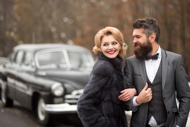 Pan młody w czarnym garniturze z kobietą na zewnątrz w pobliżu samochodu retro. romantyczna data. vintage ludzie