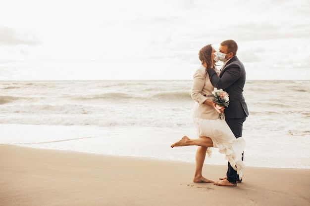 Pan młody w eleganckim garniturze i piękna panna młoda w sukni ślubnej spacerującej wzdłuż plaży. nowożeńcy całują w ochronne maski medyczne. stonowany