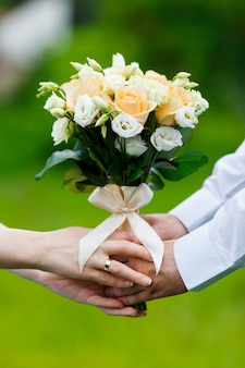 Pan młody w garniturze i panna młoda w sukience z bukietami kwiatów