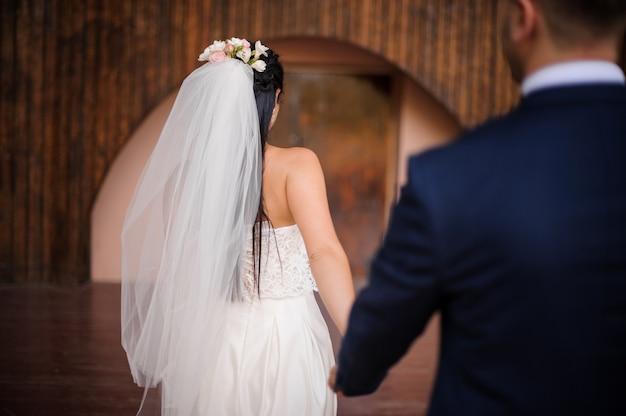 Pan młody w garniturze podążający za swoją piękną narzeczoną ubrany w białą sukienkę